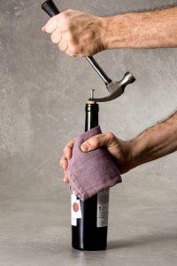 Simulação de como abrir uma garrafa de vinho utilizando um parafuso e martelo