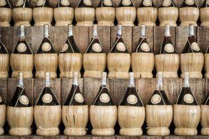 Três fileiras de garrafas de chianti tradicional com fundo de palah