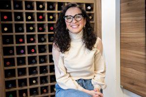 Sommelière Jessica Marinzeck sorrindo, sentada em frente a uma adega de vinhos.