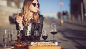 Mulher sentada olhando a paisagem com várias taças de vinho do porto na sua mesa