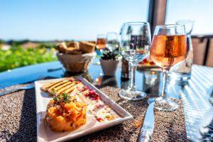 Prato com tartare de salmão e uma taça de vinho rosé ao lado