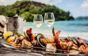 Bandeja com diversos frutos do mar com duas taças de vinho branco ao fundo