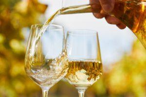 Mão servindo uma de duas taças com vinho branco
