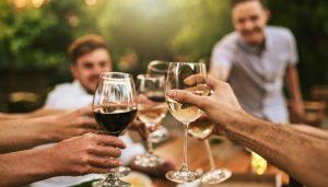 Um grupo de amigos brindando com taças de vinho